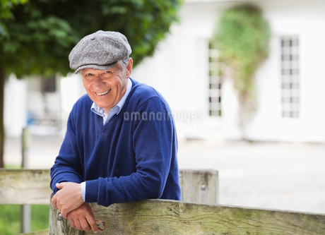 Man smiling by wooden fenceの写真素材 [FYI02184587]