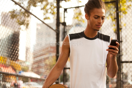 Man using cell phone on basketball courtの写真素材 [FYI02184652]