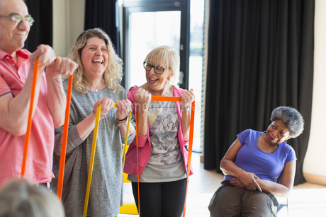 Happy instructor and active seniors exercising with strapsの写真素材 [FYI02184673]