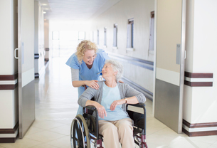 Nurse with aging patient in wheelchair in hospital corridorの写真素材 [FYI02184675]
