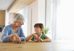 Older woman and granddaughter filling change jarの写真素材 [FYI02184744]