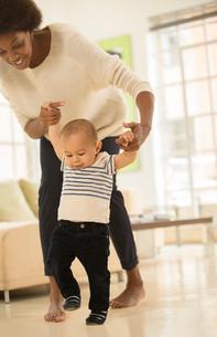 Mother helping baby boy walk in living roomの写真素材 [FYI02184752]