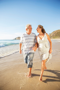 Senior couple walking in surf on beachの写真素材 [FYI02184764]