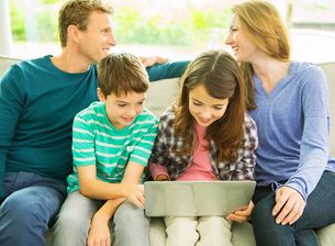 Family relaxing together on sofaの写真素材 [FYI02184791]