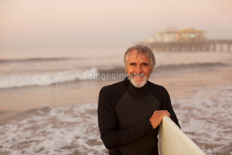 Older surfer carrying board on beachの写真素材 [FYI02184804]