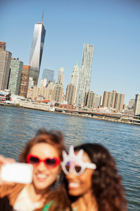 Women in novelty sunglasses taking picture by city cityscapeの写真素材 [FYI02184811]