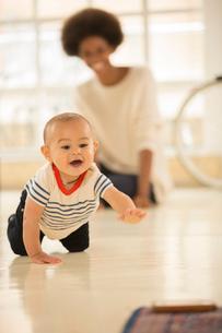 Mother watching baby boy crawl on floorの写真素材 [FYI02184814]