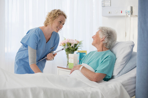 Nurse and aging patient talking in hospital roomの写真素材 [FYI02184816]
