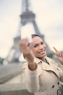 Woman taking picture in front of Eiffel Tower, Paris, Franceの写真素材 [FYI02184821]
