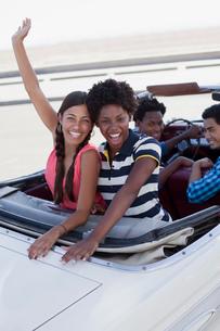 Smiling women cheering in convertibleの写真素材 [FYI02184848]