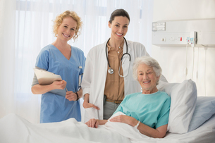 Doctor, nurse and senior patient smiling in hospital roomの写真素材 [FYI02184849]