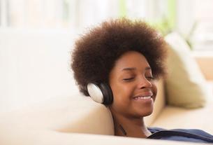 Woman listening to headphones on sofaの写真素材 [FYI02184880]