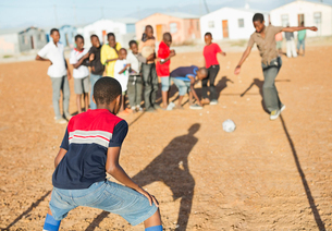Boys playing soccer together in dirt fieldの写真素材 [FYI02184913]