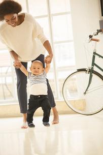 Mother helping baby boy walk in living roomの写真素材 [FYI02184914]