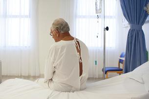 Older patient wearing gown in hospital roomの写真素材 [FYI02184916]