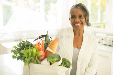 Portrait of smiling senior woman with groceries in kitchenの写真素材 [FYI02184919]