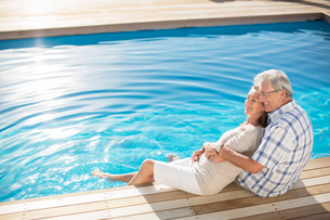 Senior couple relaxing by poolの写真素材 [FYI02184934]