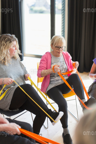Active senior woman exercising, stretching leg with strap in exercise classの写真素材 [FYI02184935]
