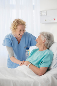 Nurse and senior patient talking in hospital roomの写真素材 [FYI02184944]