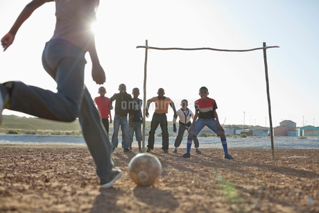 Boys playing soccer together in dirt fieldの写真素材 [FYI02184954]