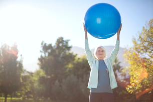 Senior woman holding fitness ball in parkの写真素材 [FYI02184980]