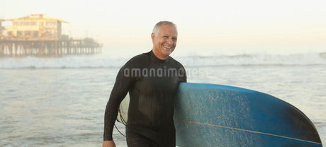 Older surfer carrying board on beachの写真素材 [FYI02184998]