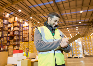 Worker writing on clipboard in warehouseの写真素材 [FYI02185014]