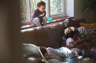 Happy father and children cuddling on living room sofaの写真素材 [FYI02185044]