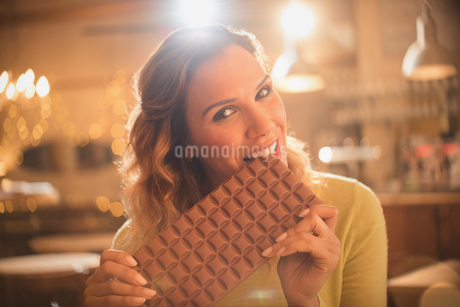 Portrait woman with sweet tooth craving biting into large chocolate barの写真素材 [FYI02185053]