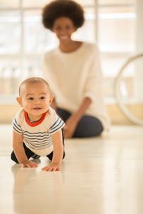 Mother watching baby boy crawl on floorの写真素材 [FYI02185064]