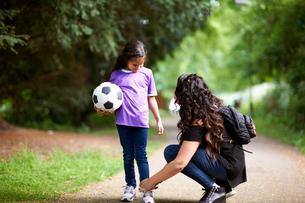 Mother tying shoelace of daughter holding soccer ballの写真素材 [FYI02185101]