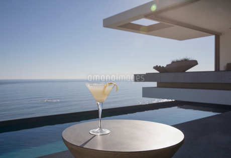 Lemon cocktail in martini glass on sunny luxury patio with ocean viewの写真素材 [FYI02185111]