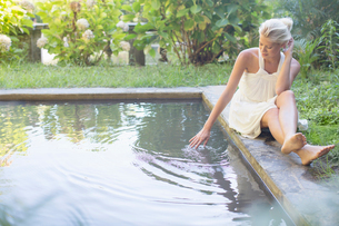 Woman relaxing by poolの写真素材 [FYI02185155]