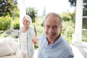 Senior couple holding hands on patioの写真素材 [FYI02185166]