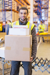 Worker carrying boxes in warehouseの写真素材 [FYI02185186]
