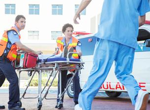 Paramedics wheeling patient in hospital parking lotの写真素材 [FYI02185245]