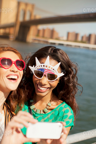 Women in novelty sunglasses taking picture by city cityscapeの写真素材 [FYI02185258]