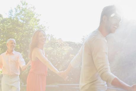 Sunbeam over friends holding hands outdoorsの写真素材 [FYI02185276]