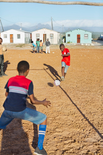 Boys playing soccer together in dirt fieldの写真素材 [FYI02185365]