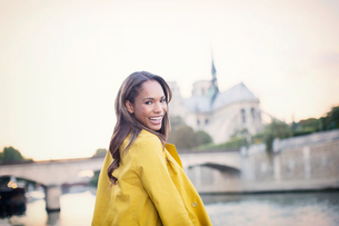 Woman smiling along Seine River near Notre Dame Cathedral, Paris, Franceの写真素材 [FYI02185376]