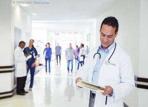 Doctor reading medical chart in hospital hallwayの写真素材 [FYI02185390]
