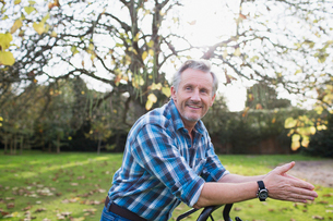 Portrait confident senior man mowing autumn lawn in backyardの写真素材 [FYI02185396]