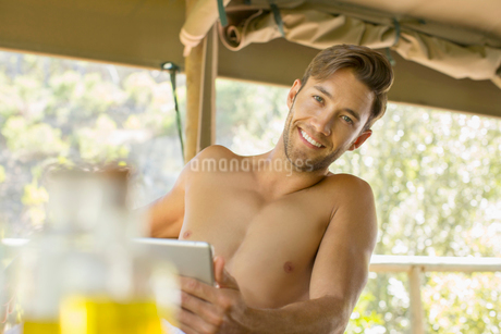Man using digital tablet on balconyの写真素材 [FYI02185401]