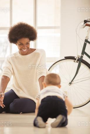 Mother watching baby boy crawl in living roomの写真素材 [FYI02185412]