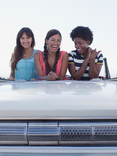 Smiling women sitting in convertibleの写真素材 [FYI02185417]