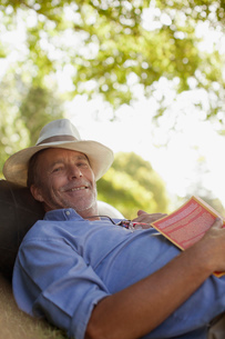 Portrait of smiling man laying in grass with bookの写真素材 [FYI02185437]