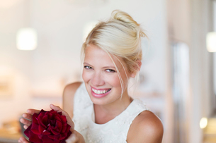 Smiling woman holding red flowerの写真素材 [FYI02185438]