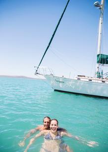 Couple swimming in water near boatの写真素材 [FYI02185451]