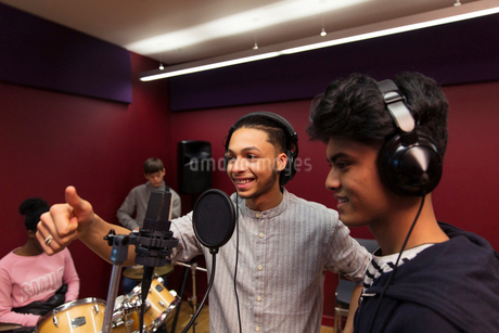 Smiling teenage musicians recording music, singing in sound boothの写真素材 [FYI02185475]