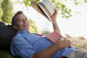 Portrait of smiling man laying on grass with book and hatの写真素材 [FYI02185490]